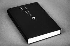 Cross with a chain on the closed Holy Bible. Christian cross with a chain on a closed book. The Holy Bible in black and white. The Way to God through Prayer and stock photography