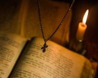 The cross hangs over a prayer book with a burning candle Royalty Free Stock Photos