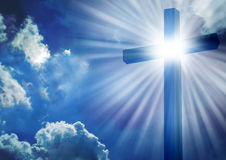 The Cross. Christian cross with bright sun and clouds background Royalty Free Stock Photo