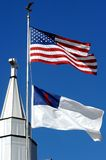 Cross and Christian Flag. Cross tops a metal steeple. Two flags fly besides steeple. One is the Chrisian Flag and the other is the American Flag. Blue skies stock image