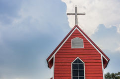 Cross church with red building and blue sky | Christian religion place and symbol Royalty Free Stock Image