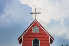 Cross church with red building and blue sky | Christian religion place and symbol Stock Photo