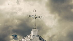 Cross church sky bad clouds. An old stone church under a sky of dark clouds. Detail of the iron cross on the top. Timelapse stock video footage