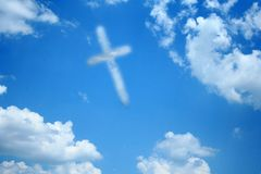Cross Cloud. A cloud in the shape of a cross floats among other clouds in the sky Stock Images