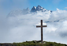 Cross in the clouds. Wooden cross in the clouds on a background of snowy peaks in the Swiss Alps Stock Photography