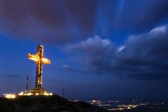 Cross and clouds. The millennium cross on top of mt. Vodno in Skopje, Macedonia, at night with clouds passing above it and the city lights behind it Royalty Free Stock Image