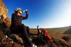 Cross country biker drinking water with bike, sky background. side view Royalty Free Stock Image