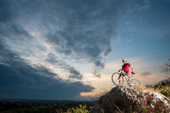 Cross country biker relaxing on the top of the mountain. Young man athlete standing on top of a mountain with bicycle and enjoying view, with sky background Stock Images
