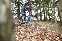 Cross-country cyclist descending a slope, selective focus Stock Photo