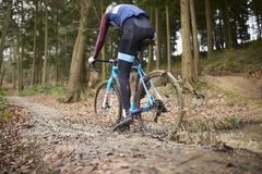 Cross-country cyclist riding in mud, low angle back view Royalty Free Stock Photography