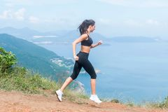 Cross-country female runner trail running on mountain path in summer. Woman wearing black sportswear exercising outdoors Stock Photography