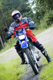 Cross-country motorbike. A proud rider of a motorbike, country road background. Diagonal composition Stock Image