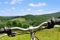 Cross-country mountain biking. View over the handle bars of a mountain bike high on a hill royalty free stock image