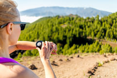 Cross country runner looking at sport watch Royalty Free Stock Images