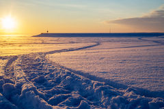 Cross country ski trace towards pier at sunset. Beautiful winter scene. Royalty Free Stock Image