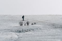 Cross-country skier in mountains on the peak of a hill. On horizon. Snowing Royalty Free Stock Images