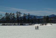 Cross Country Skiiers. Two people cross country ski across a frozen lake in New Hamshire Stock Images