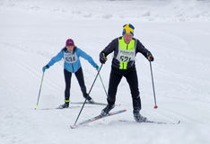 Cross country skiing man wearing swedish hat and woman skiing up Royalty Free Stock Photography