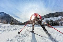 Cross-country skiing. Young man doing outdoor exercise. Winter sport and healthy lifestyle. Backside view Royalty Free Stock Photography