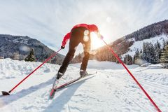 Cross-country skiing. Young man doing outdoor exercise. Winter sport and healthy lifestyle. Backside view Royalty Free Stock Photos