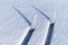 Cross-country skis in a friable snow. Fragments of cross-country skis in a friable snow with shadows Royalty Free Stock Photo