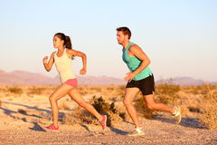 Cross-country trail running people at sunset. Runner couple exercising outside as part of healthy lifestyle. Multiracial runners couple, Asian woman, Caucasian Stock Photography