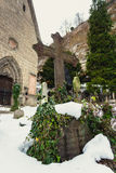 Cross covered by snow on ancient graveyard at church Royalty Free Stock Images