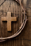 Cross and crown of thorns of Jesus Christ. High-angle shot of a small wooden cross and a depiction of the crown of thorns of Jesus Christ on a wooden surface Royalty Free Stock Photography