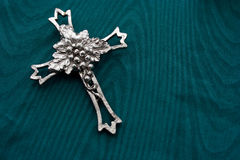Cross or crucifix. Silver cross or crucifix on green background Stock Photos
