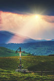 Cross with crucifix on a hil. L in a Carpathian mountain valley. Ray of light lay on a hill. Colorful dramatic sunset. Ukraine, Europe royalty free stock images
