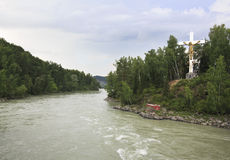 Cross with crucifix on the island of the Katun River. Stock Photos