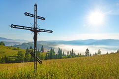 Cross-crucifixion in the field on a sunny day with fog. In the mountains (pilgrimage, harmony, inspiration, peace - concept Royalty Free Stock Image
