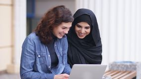 Cross-cultural friendship. Young muslim woman in black hijab is talking to her female caucasian friend. Two attractive. Young women sitting outside and using stock video