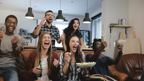 Cross-cultural group watch sports game on TV. Passionate supporters celebrate goal with drinks. 4K slow motion close up. royalty free stock image