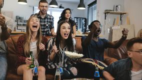 Cross-cultural group watch sports game on TV. Passionate supporters celebrate goal with drinks. 4K slow motion close up. Emotion euphoria. World Championship Stock Photo