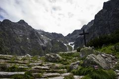 Cross on the Czarny Staw lake in Tatra Mountains stock images
