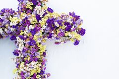 Cross decorated with colorful flowers on white wall