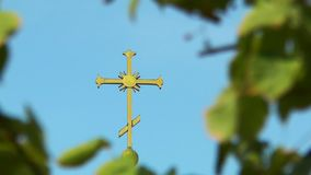 The cross on the dome among leaves. Against the blue sky stock footage