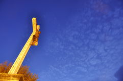 Cross at dusk. Low perspective upward of a religious cross with a sky background Stock Photo