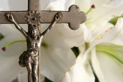 Cross and easter lilies. Old cross on white easter lilies background Royalty Free Stock Images