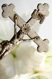 Cross and easter lilies. Old cross on white easter lilies background Royalty Free Stock Photo