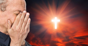 Cross and elderly man with a face closed by hands. Elderly man with a face closed by hands on the background of the sky with a cross, a symbol of faith royalty free stock image