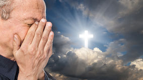 Cross and elderly man with a face closed by hands. Elderly man with a face closed by hands on the background of the sky with a cross, a symbol of faith stock photography