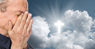 Cross and elderly man with a face closed by hands. Elderly man with a face closed by hands on the background of the sky with a cross, a symbol of faith royalty free stock photos