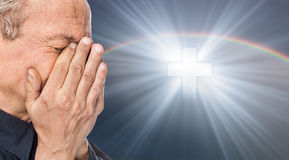 Cross and elderly man with a face closed by hands. Elderly man with a face closed by hands on the background of the sky with a cross, a symbol of faith royalty free stock photography