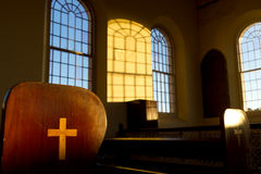 Cross on end of pew in historic chapel Royalty Free Stock Photos
