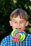 Cross eyed boy eating lollipop Royalty Free Stock Image