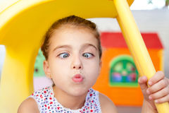 Cross eyed squinting expression little girl. In playground Royalty Free Stock Photos