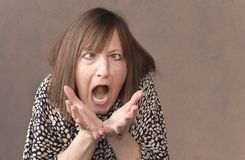 Cross eyed woman lets out her pent up anger. Angry woman screaming with rage, furious and dangerous Royalty Free Stock Photo