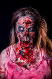 Cross-eyed Zombie girl. Portrait of zombie girl with crossed eyed and bloody makeup with latex prosthesis royalty free stock image